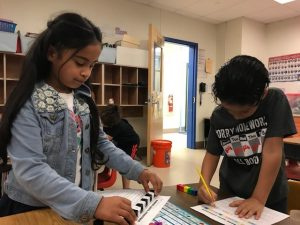 Two young students writing and using manipulatives
