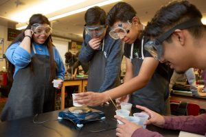 Four Students Doing a Science Experiement