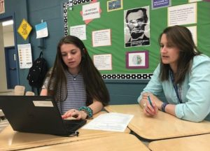 Epping High School teacher Katie Closs reviews a student's collection of evidence during a student-led conference related to work study practices