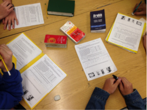Students use dictionaries in an array of languages to support their collaborative work.