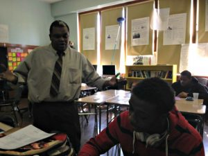 Teacher Erick Delcham discussing math concepts with a student at North Queens Community High School