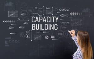 "Woman writing ""capacity building"" on chalkboard"