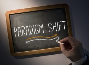 Hand writing the word paradigm shift on black chalkboard